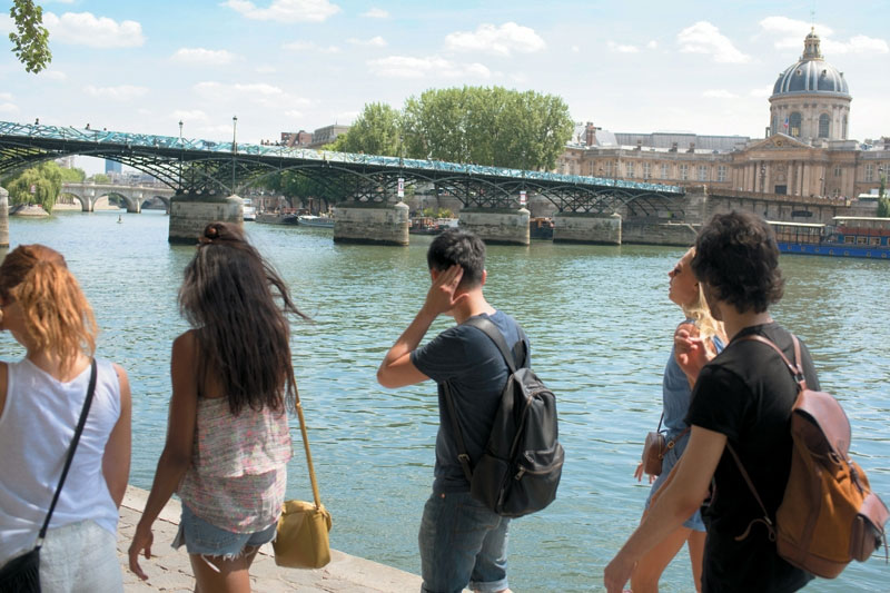 Young travelers walk along the Seine River in Paris