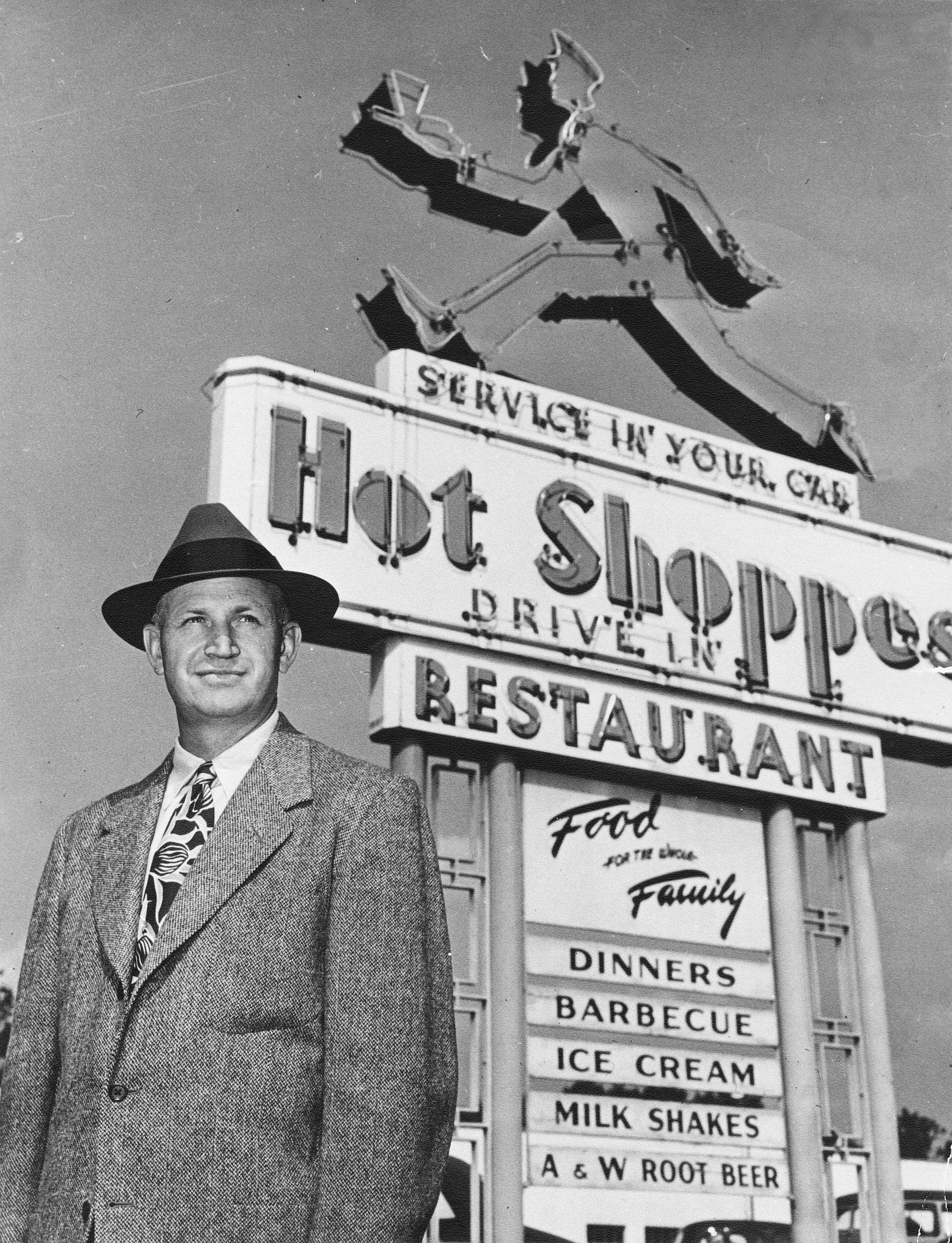 J. Willard Marriott, Sr. in front of Hot Shoppes sign.