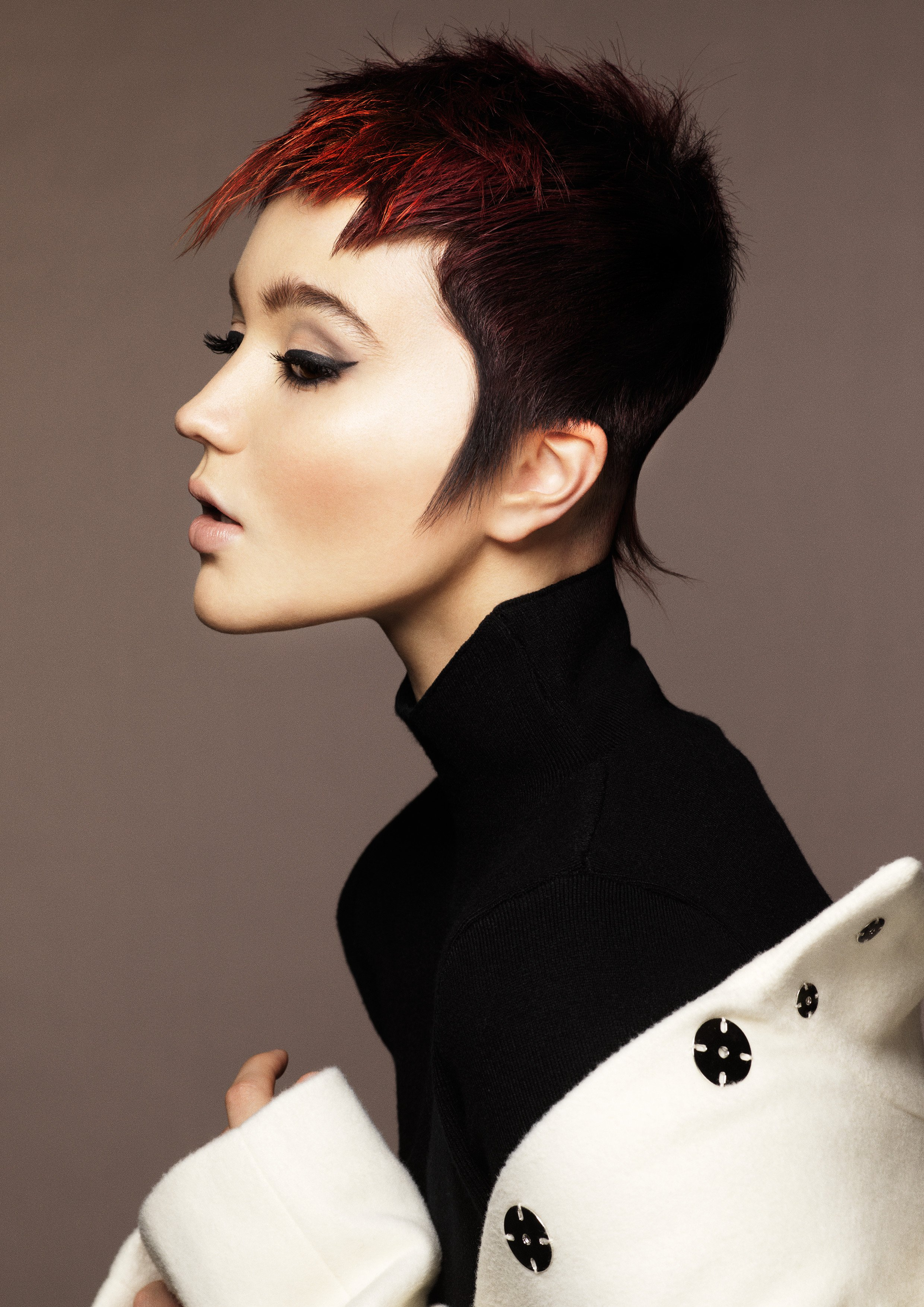 """Iconic short haircut. Dark base with hints of caramel and burgundy."""