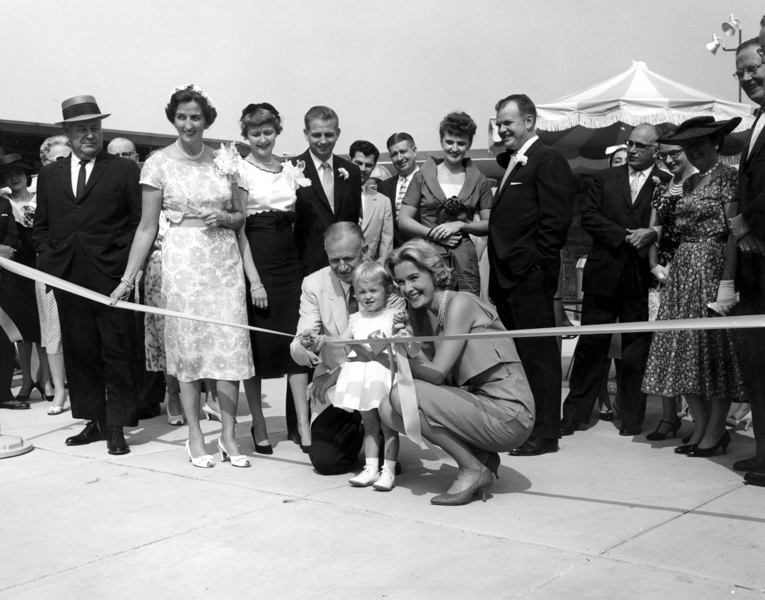 The Marriott family, with Bill Marriott standing behind his father, opening the company's second hotel, the Key Bridge Marriott.