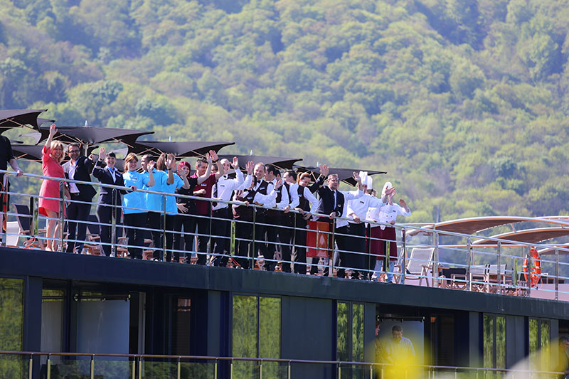AmaWaterways Senior Vice President, Co-Owner and AmaKristina Godmother Kristin Karst, Leonardo Starico from the company's Basel office, and the ship's crew wave to the crowd gathered in Lahnstein, Germany as the AmaKristina docks for its christening festivities.