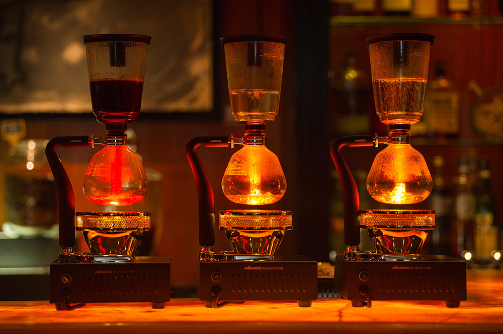 The coffee is brewed from an old-school glass Siphon, the original vacuum coffee maker invented in the 1800s as an alternative to boiling coffee.