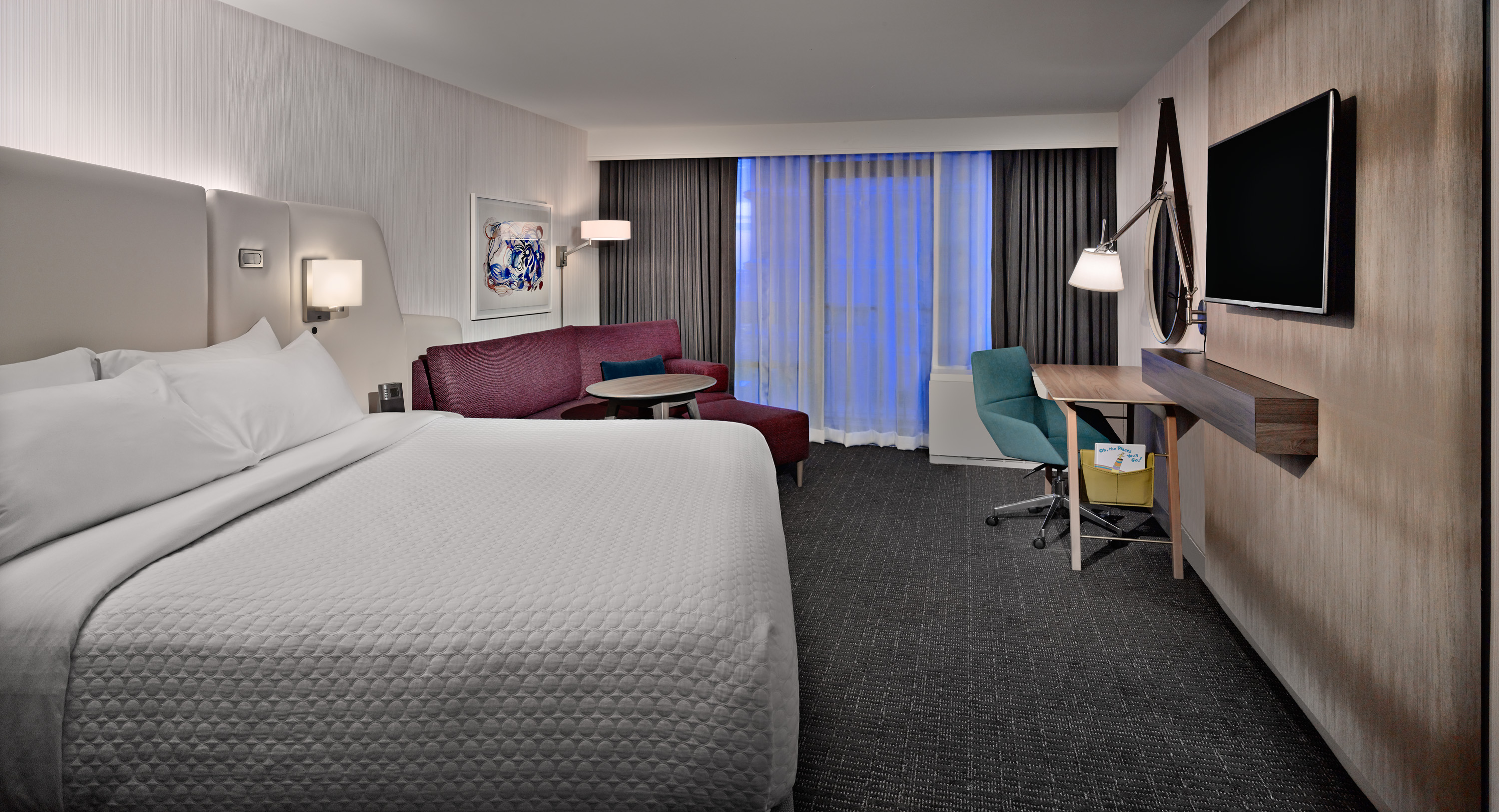 WorkLife guestrooms with king beds have sofas with a chaise lounge and a large table.