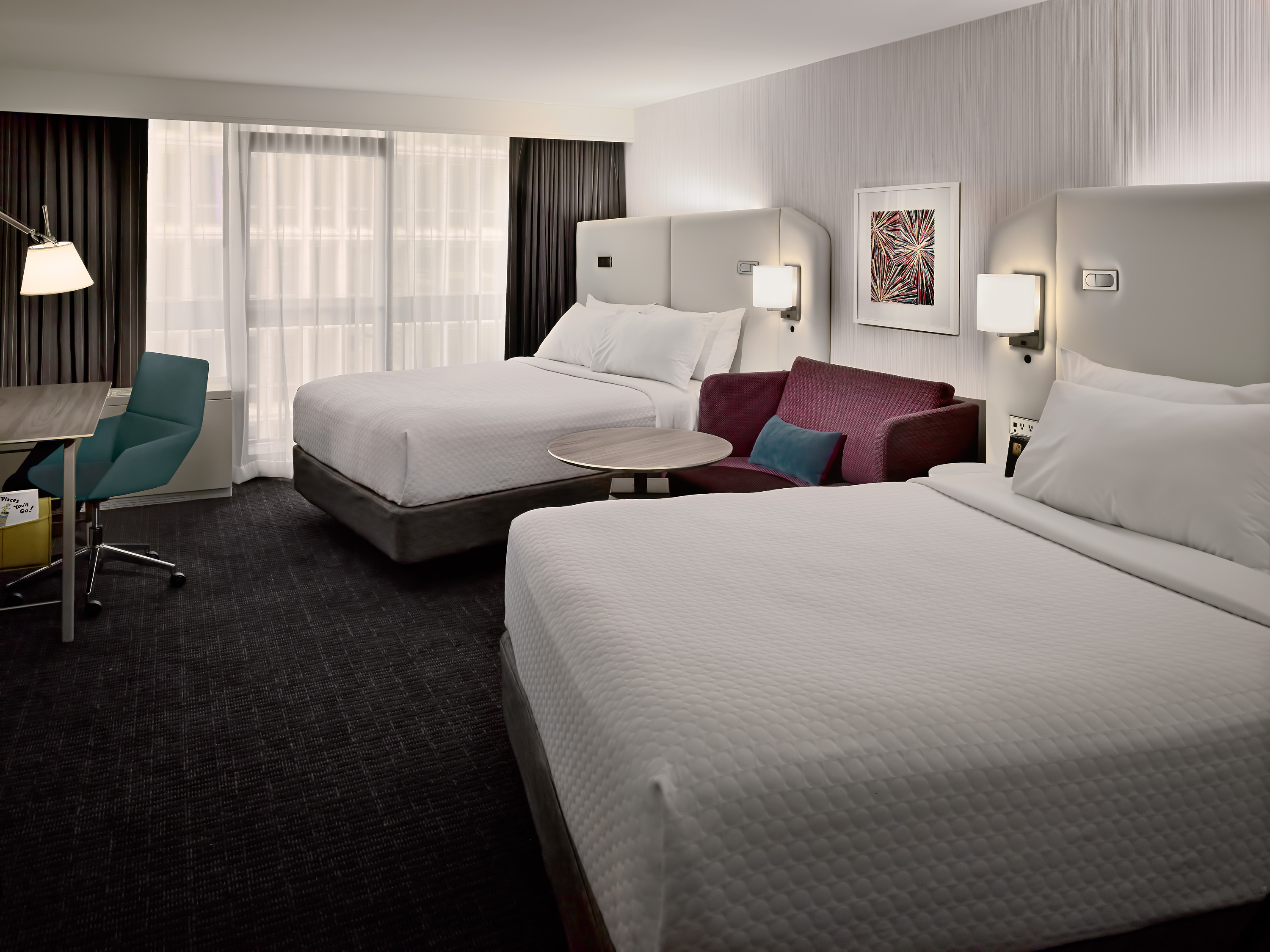Queen WorkLife guestrooms have two beds angled towards each other with a loveseat in between.