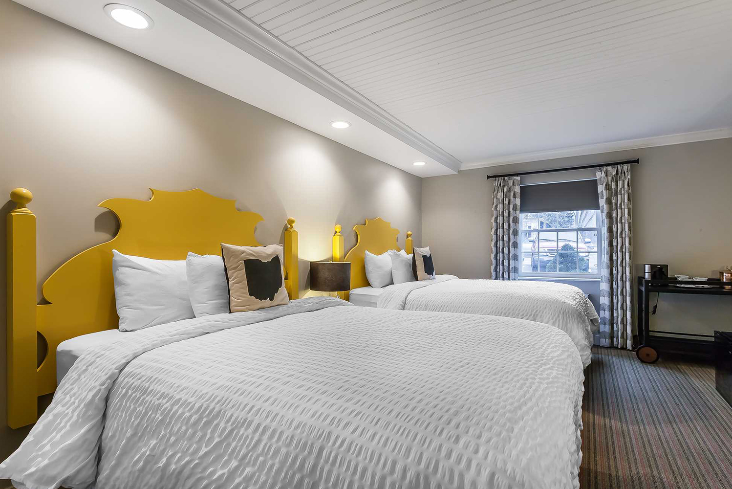 The inn's color scheme includes shades of white, grey, black and off-black, with pops of vibrant color for contrast.