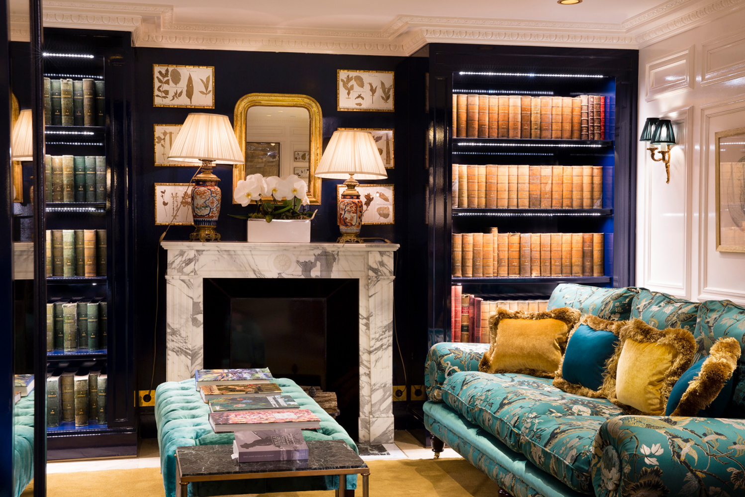 The ground floor loungeshave large armchairs and sofas, paintings and drawings, bookcases and trims, as well as mantled fireplaces and tables.