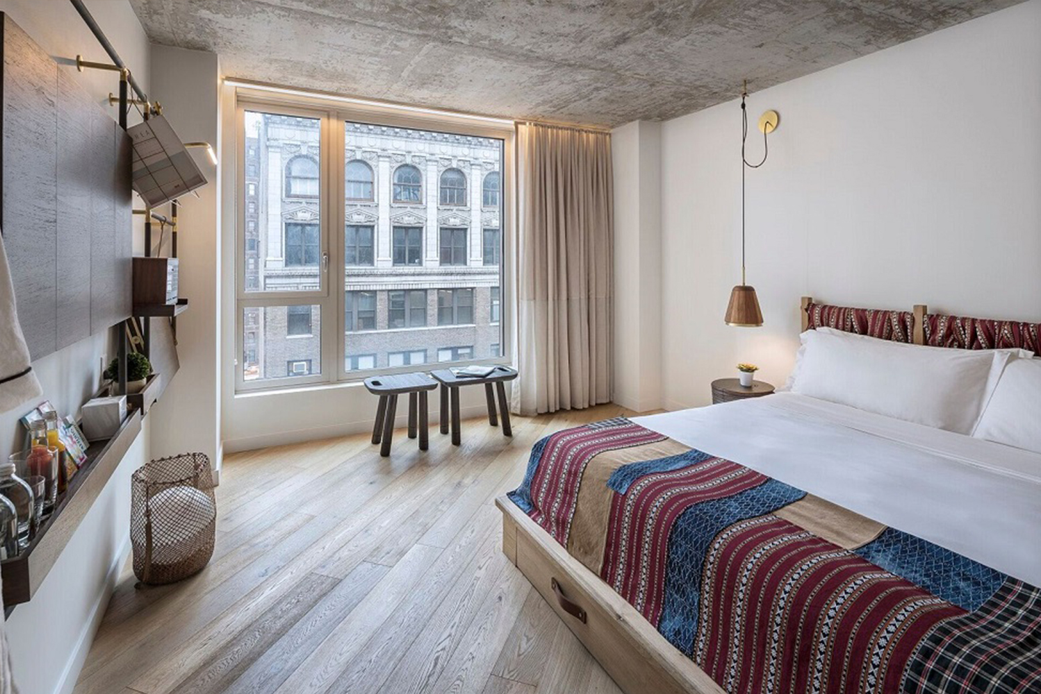 The rooms have exposed custom raw-bronze shelving and handwoven fabrics that create a backdrop for a multi-directional day bed platform.