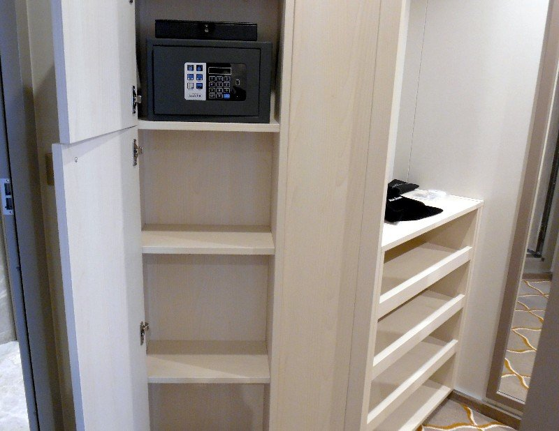 Walk-in closet with shelving, plus adjacent safe and cupboard area