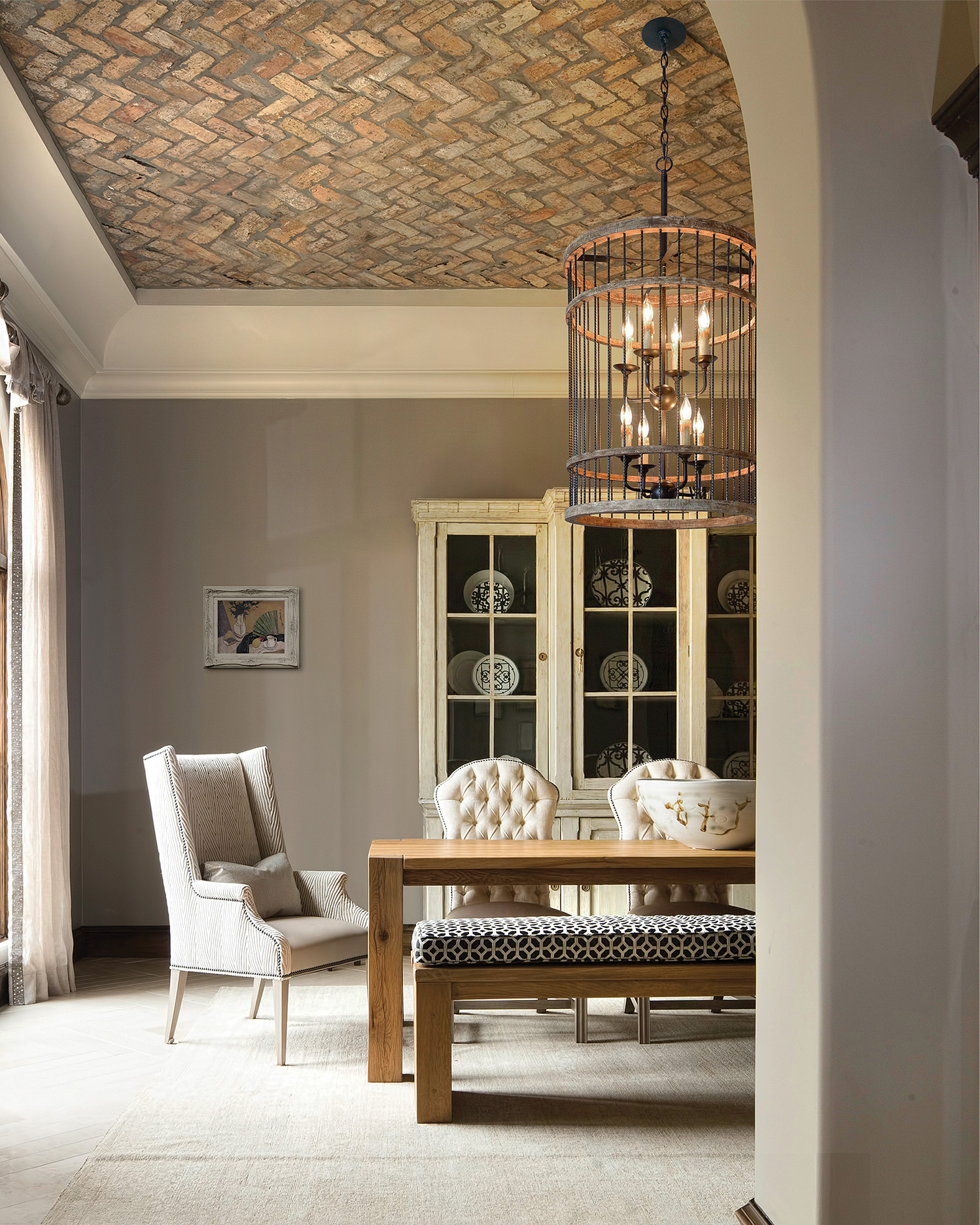 The cylindrical pendant is comprised of solid, twisted handcrafted iron rods arranged vertically and drilled through rows of stained salvaged wooden rings on the top and bottom.