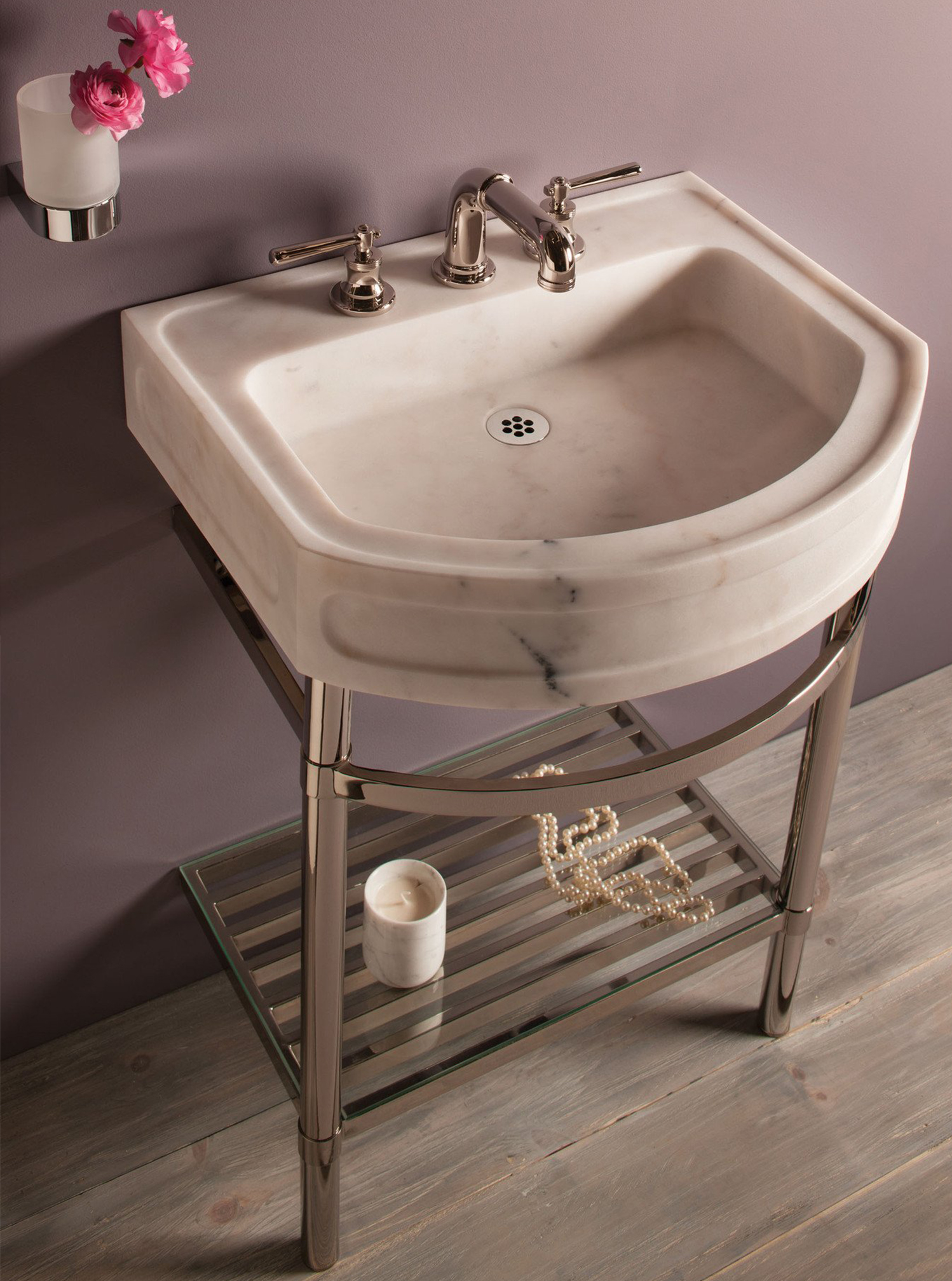 """The 24"""" wide Harbor washbasin has a curved front profile on a polished nickel stand with a shelf."""