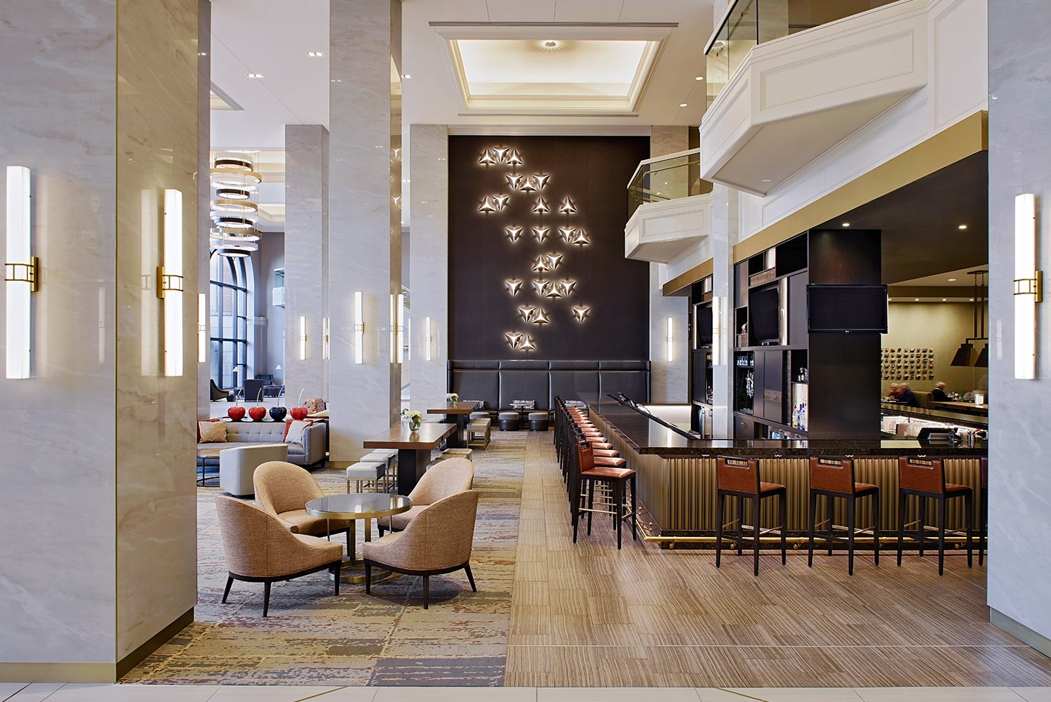 The light palette of the lobby is enhanced with walnut and dark chocolate wood finishes and colorful rich textiles.