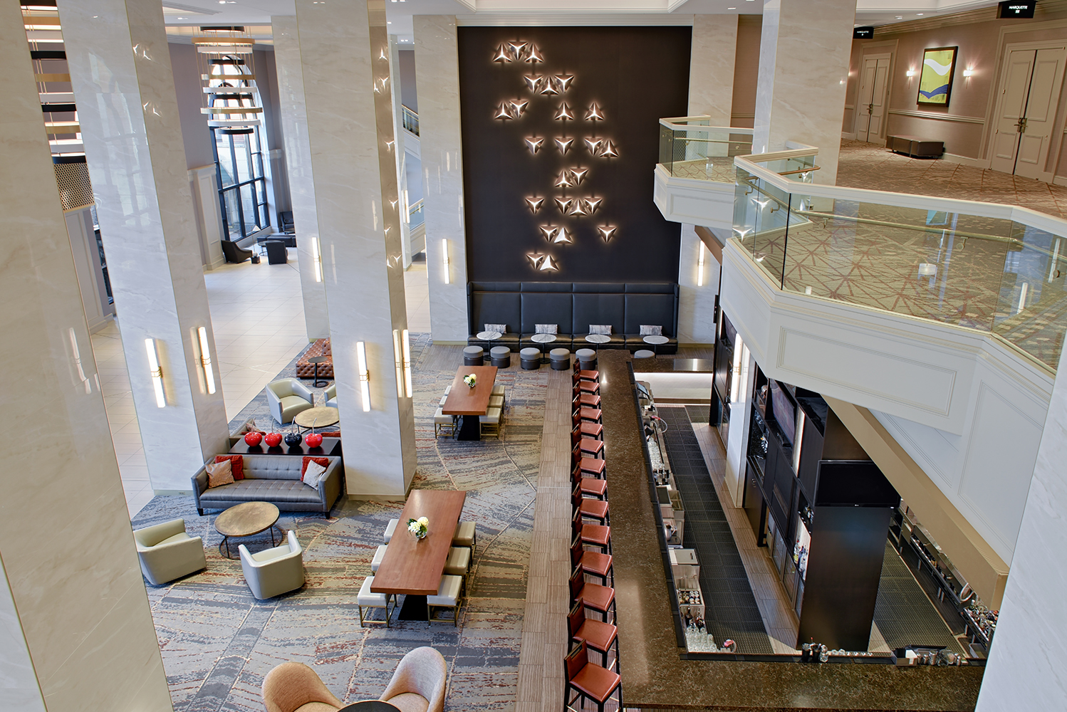 The design team preserved the original high ceilings and large arching windows of the lobby, though they also applied a mix of finishes throughout the space.
