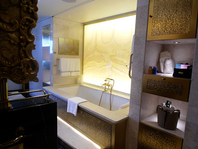 Master Bedroom Complex: The master bathroom's tub area has an elegant golden wall with soothing illumination.