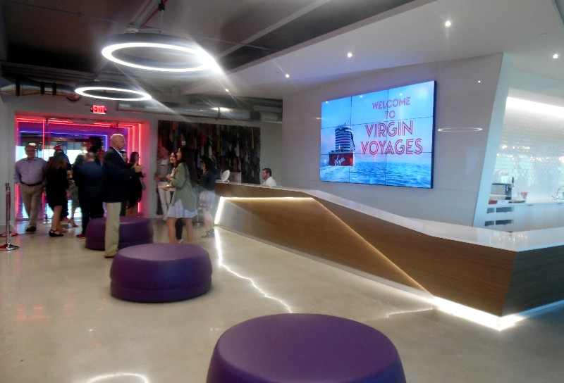Visitors who enter the Virgin Voyages offices will encounter this reception desk and purple, backless seating.