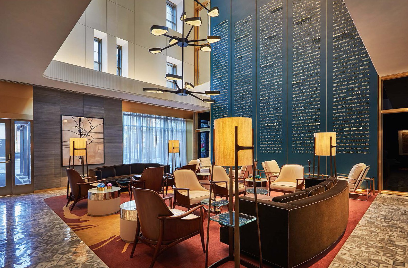 The lobby space uses white marble, brass light fixtures, and a custom 30-foot art wall tableau.