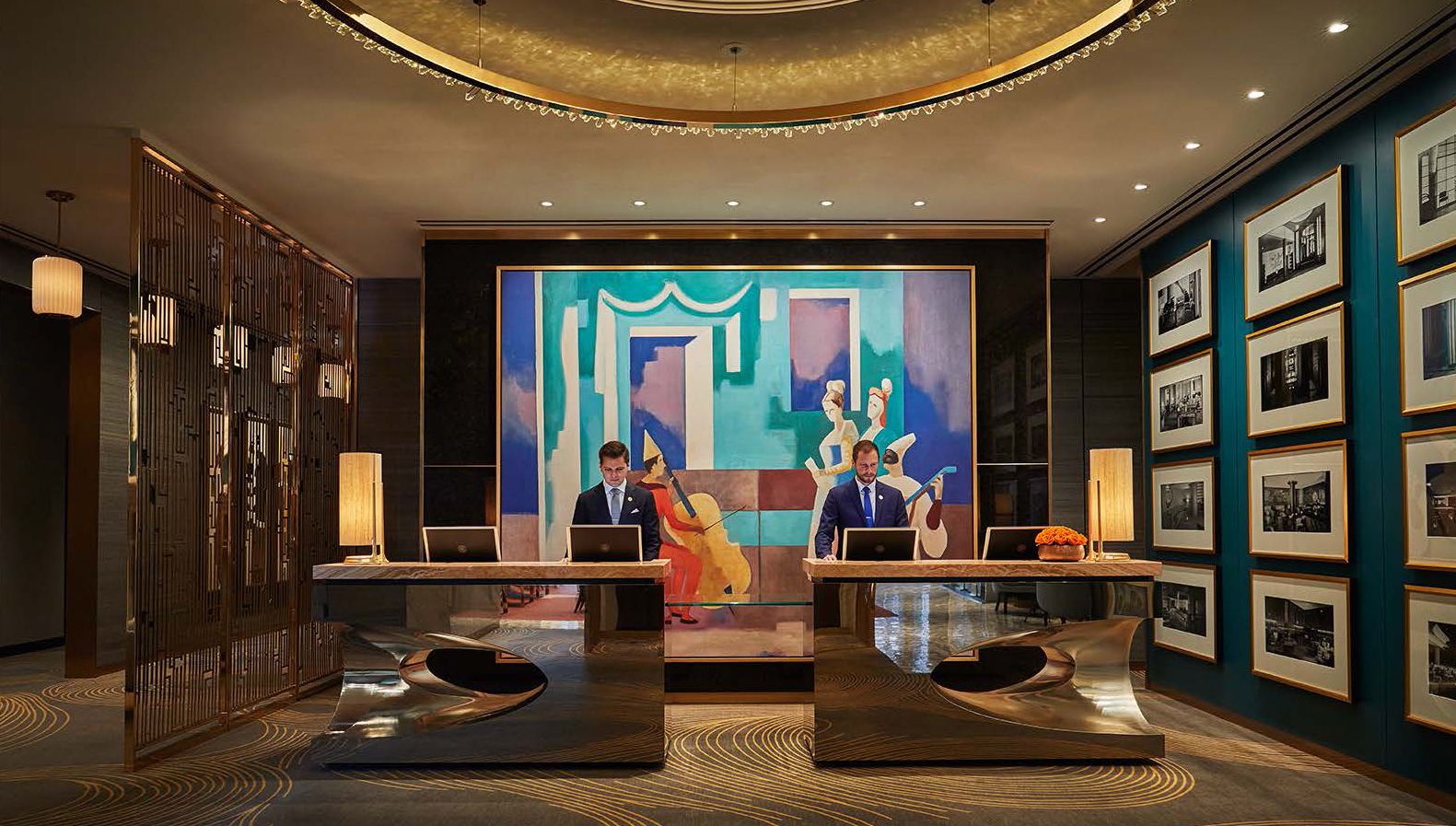 Large bronze reception desks are positioned in front of a large painting depicting a Venetian carnival recital.