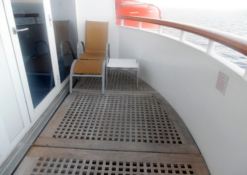 Suite private balcony. It has this lounger and table on one side and a second one at the other end.