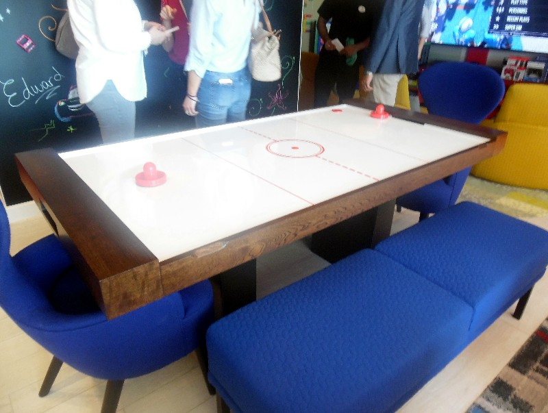An air hockey table doubles as a dining room table, with special inserts that cover the playing surface