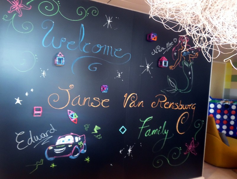 A large blackboard offers a personalized welcome greeting to guests.