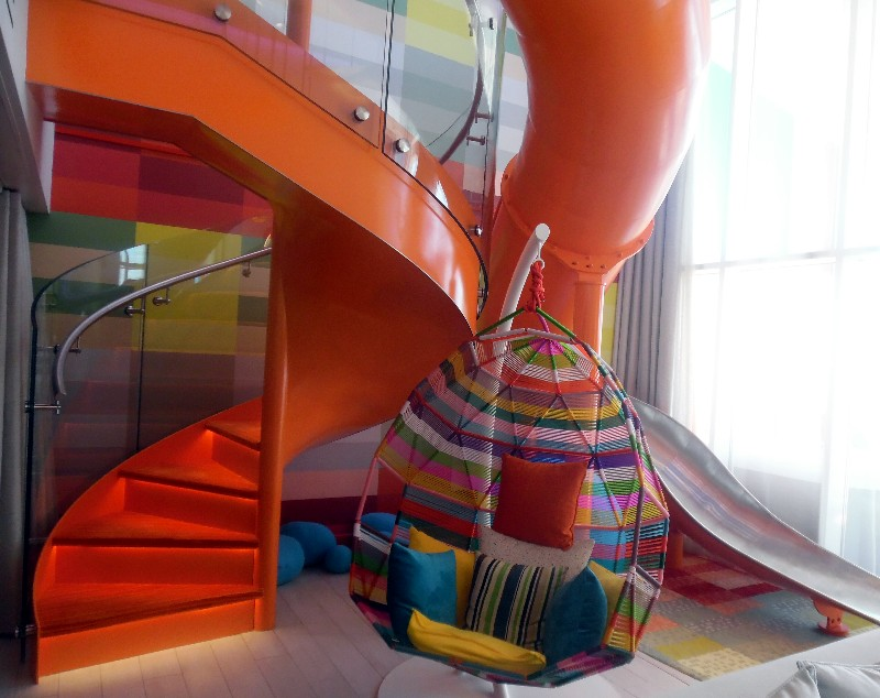 Both a spiral staircase and slide extend from the living room to the children's bedroom in the loft.