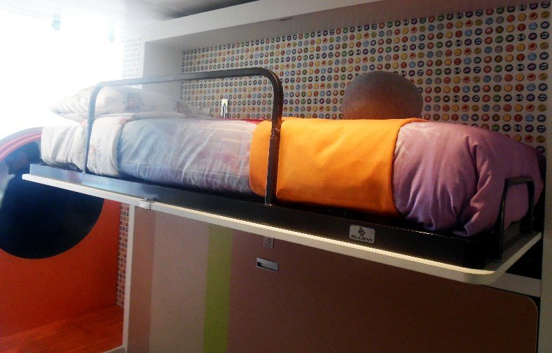 A second bunk is shown plus the opening to the slide at left; the slide zips kids down to the first level.