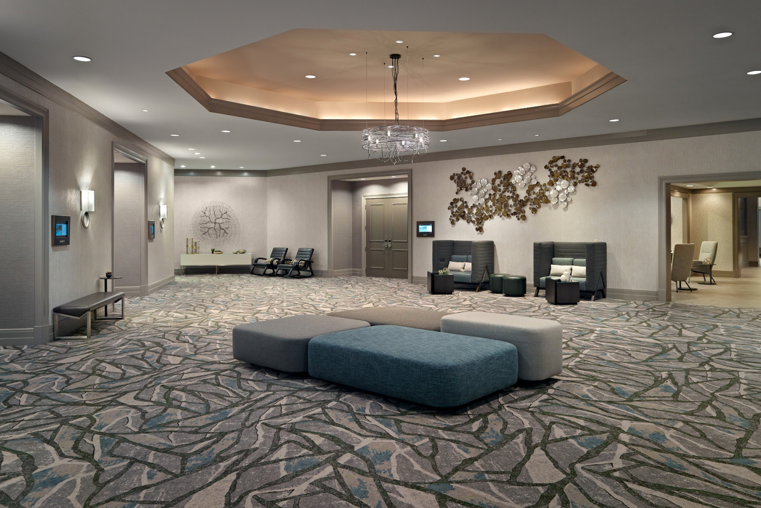 Illuminated by multi-tier custom-designed pendant chandeliers, the space has both traditional and modern elements.