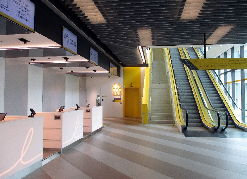 Brightline's Fort Lauderdale ticket counter area is bright and airy, and escalators lead up to the security scan area.
