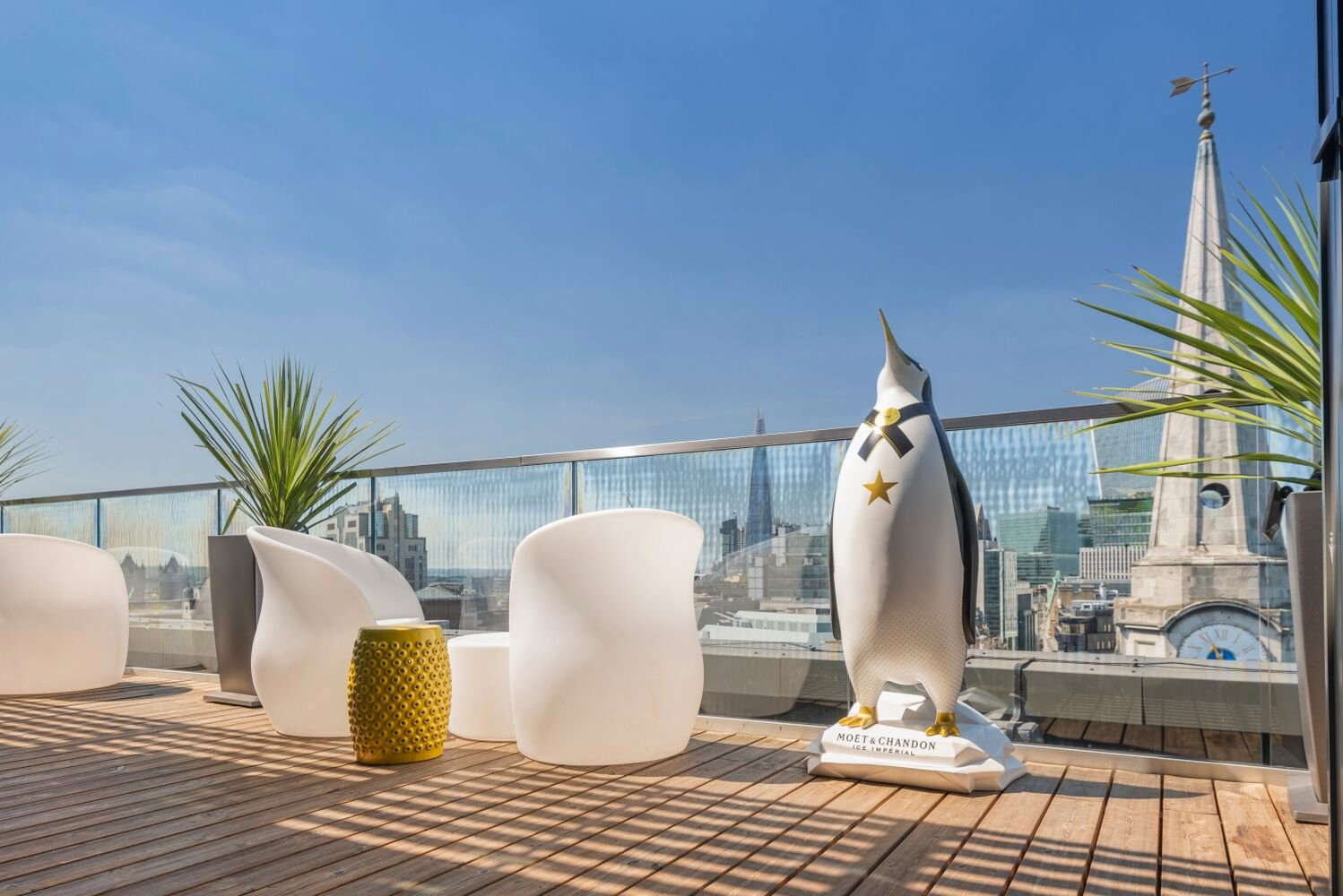 Lined with backlit furniture and a linked balcony, the rooftop deck is playful and modern.