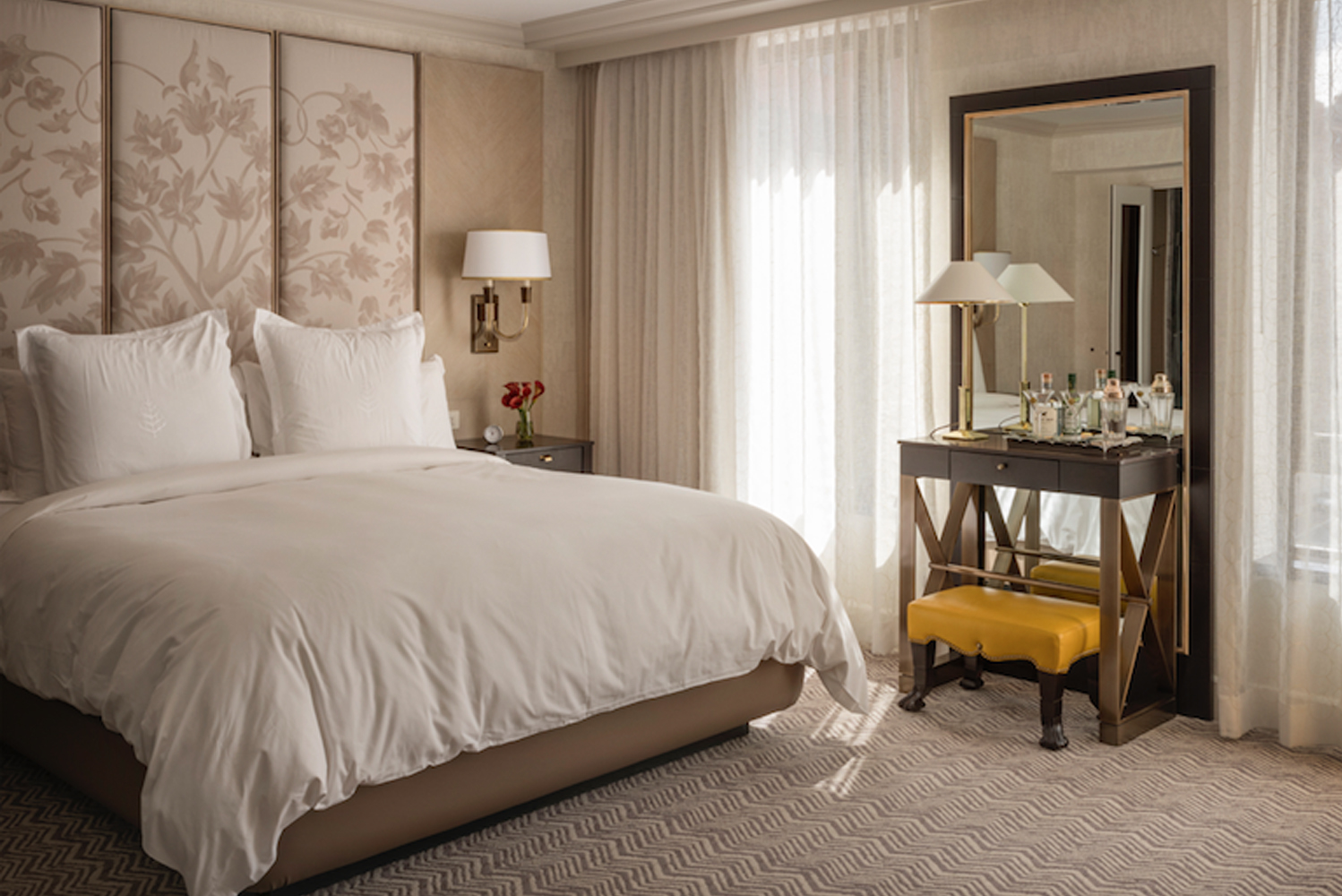 There is a headboard of whitewashed oak and upholstered inset panels, as well as eclectic groupings of mirrors and artworks.
