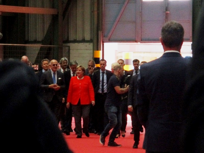 German Federal Chancellor Angela Merkel enters the building on a red carpet to claps from shipyard workers. Photo by Susan J. Young