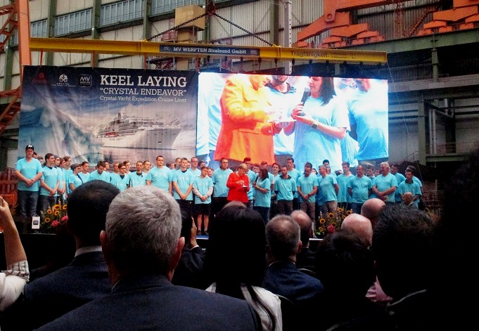German Federal Chancellor Angela Merkel joins shipyard workers on stage. Photo by Susan J. Young