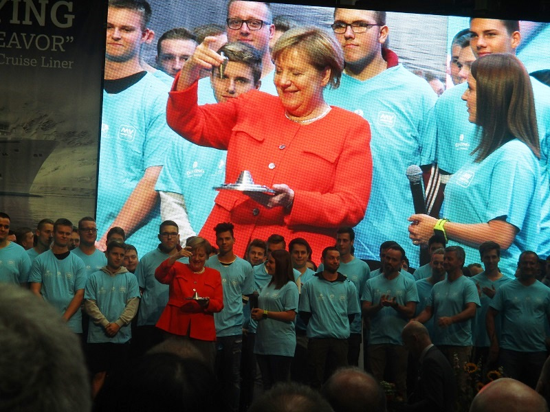 Chancellor Merkel interacts with new shipyard apprentices and workers on stage. Photo by Susan J. Young