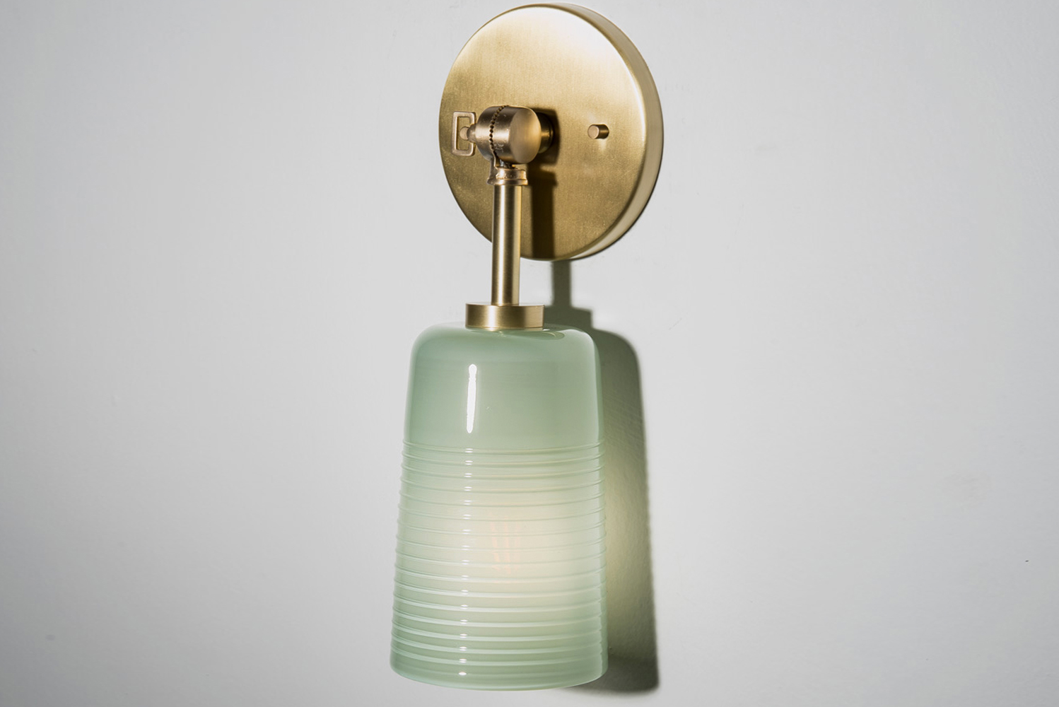 The cone shape diffuser in half-Wrap pattern has a clear-color glass, with a round backplate with brushed brass finish.