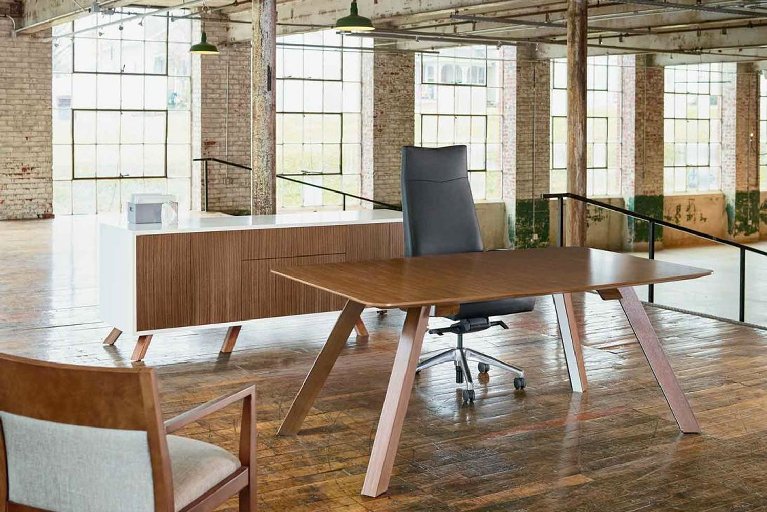 Each desk top is available in a number of materials, including wood, stone and painted glass, and the metal legs are covered with magnetized walnut veneer.