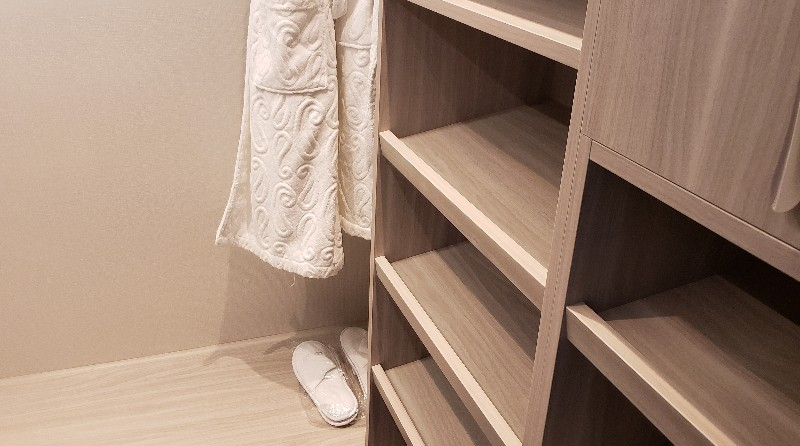 The walk-in closet has many shelves, along with hanging space and drawers