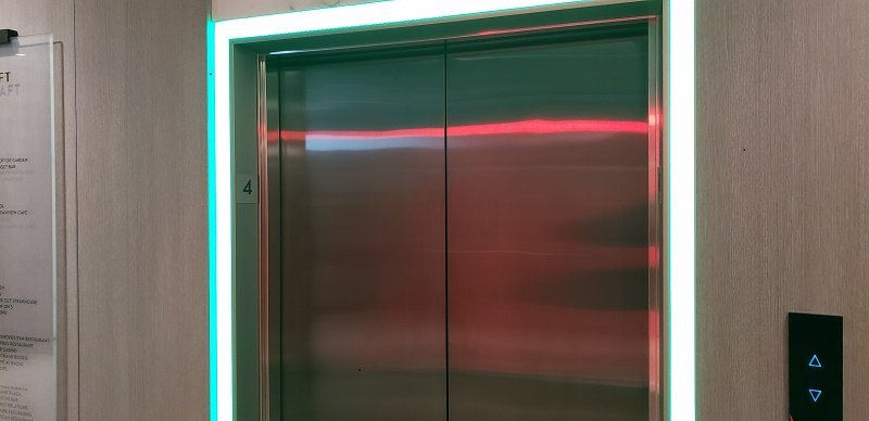 Celebrity Edge has a simple, effective elevator system -- green means the car is headed upward, red (as in the reflection seen here from across the corridor) shows a car is going down.