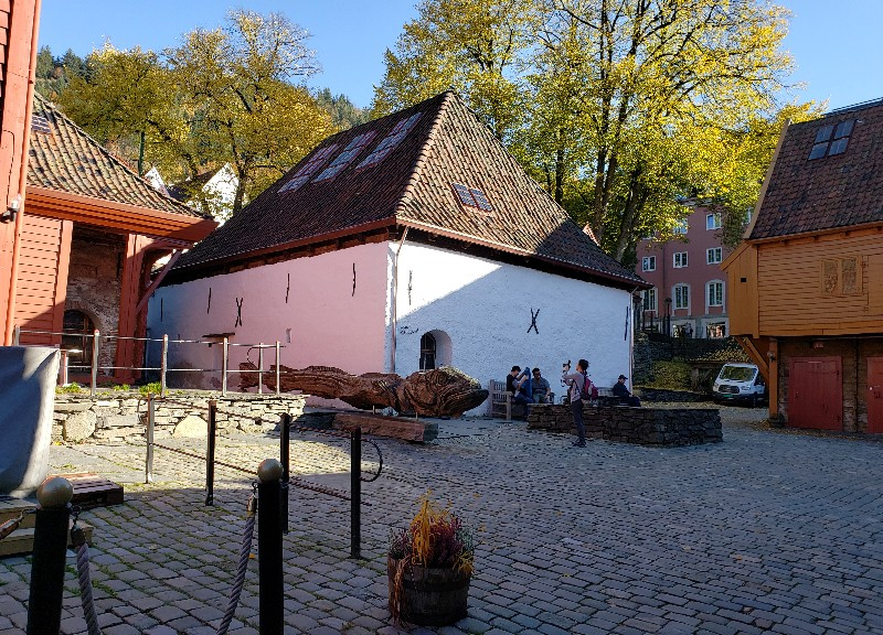 One Bryggen passageway leads to this courtyard, with a massive wooden fish carving.