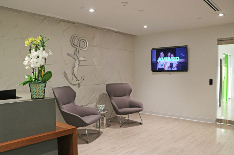 The front lobby of the office offers seating and a television.