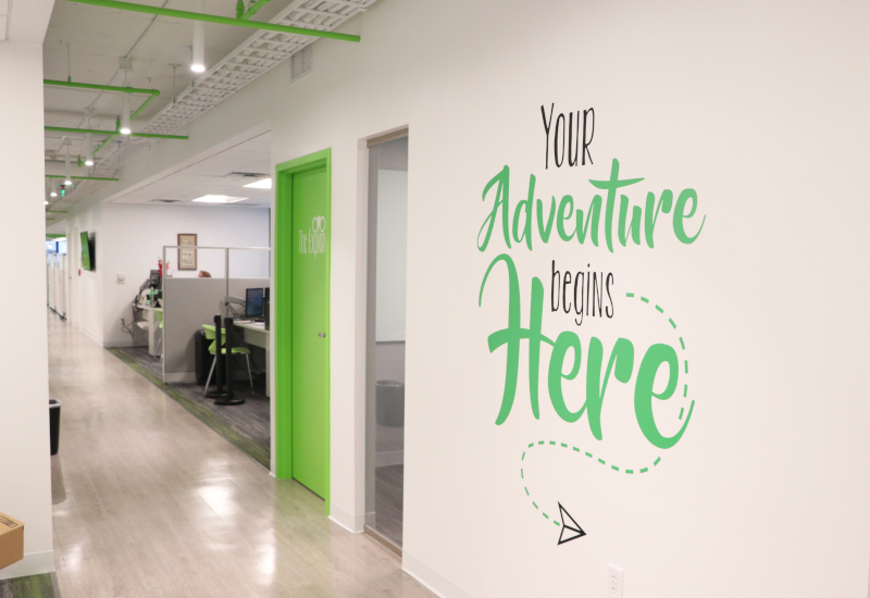 "An office hallway with ""your adventure begins here"" painted on the wall."