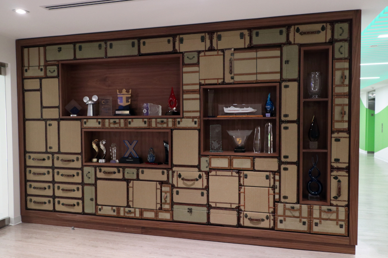 This custom luggage wall acts a trophy case for Cruise Planners.