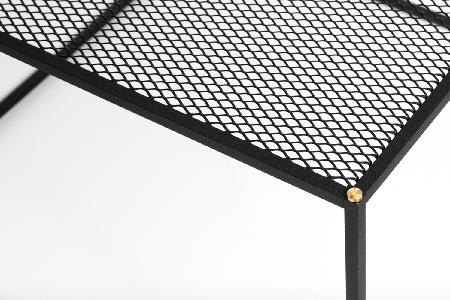 Each piece is crafted from solid black steel and perforated mesh, constructed to diffuse surrounding walls and floors, rather than hide them.