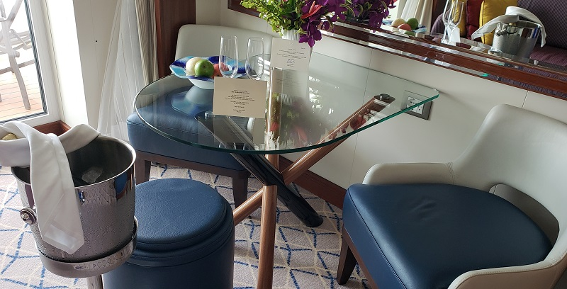 Dining area with glass table, two chairs and a stool