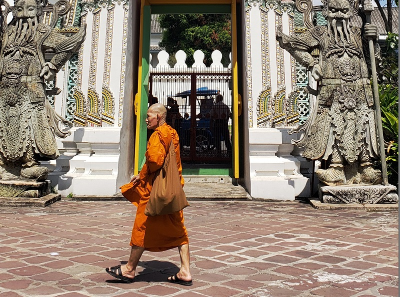 A Buddhist monk strolls through the Wat Pho complex.