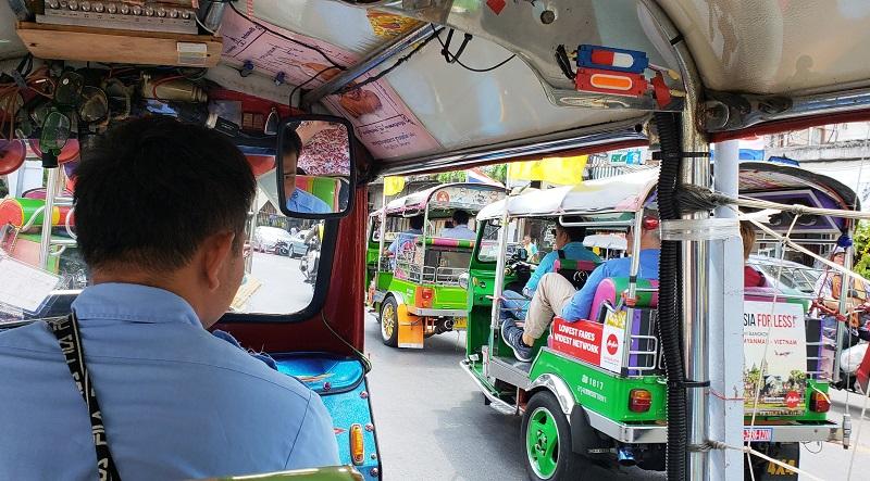 A tuk-tuk driver heads out into Bangkok traffic.