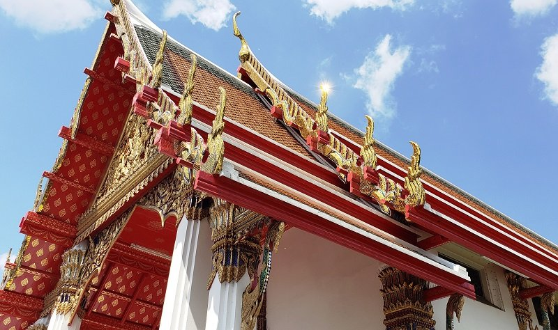 A temple's red roof with gilded decoration at the Wat Pho complex.