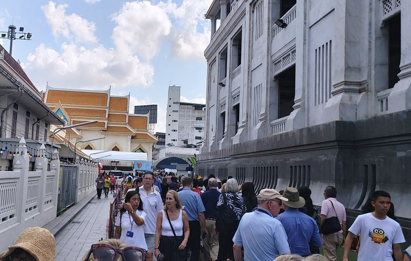 Crowds of tourists entering the Wat Traimit complex in Bangkok
