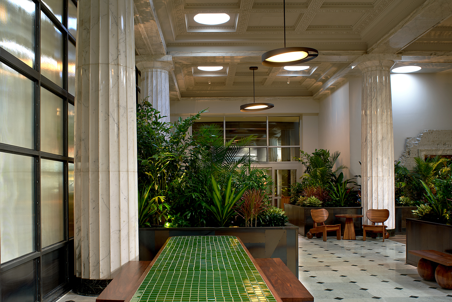 The lobby of the property is reminiscent of an indoor/outdoor garden with greenery.