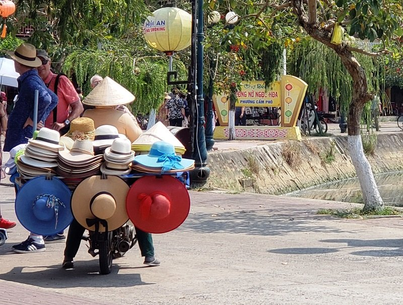 "Vendors in Hoi An get an ""A"" for creative approaches, such as this woman selling hats from a scooter."