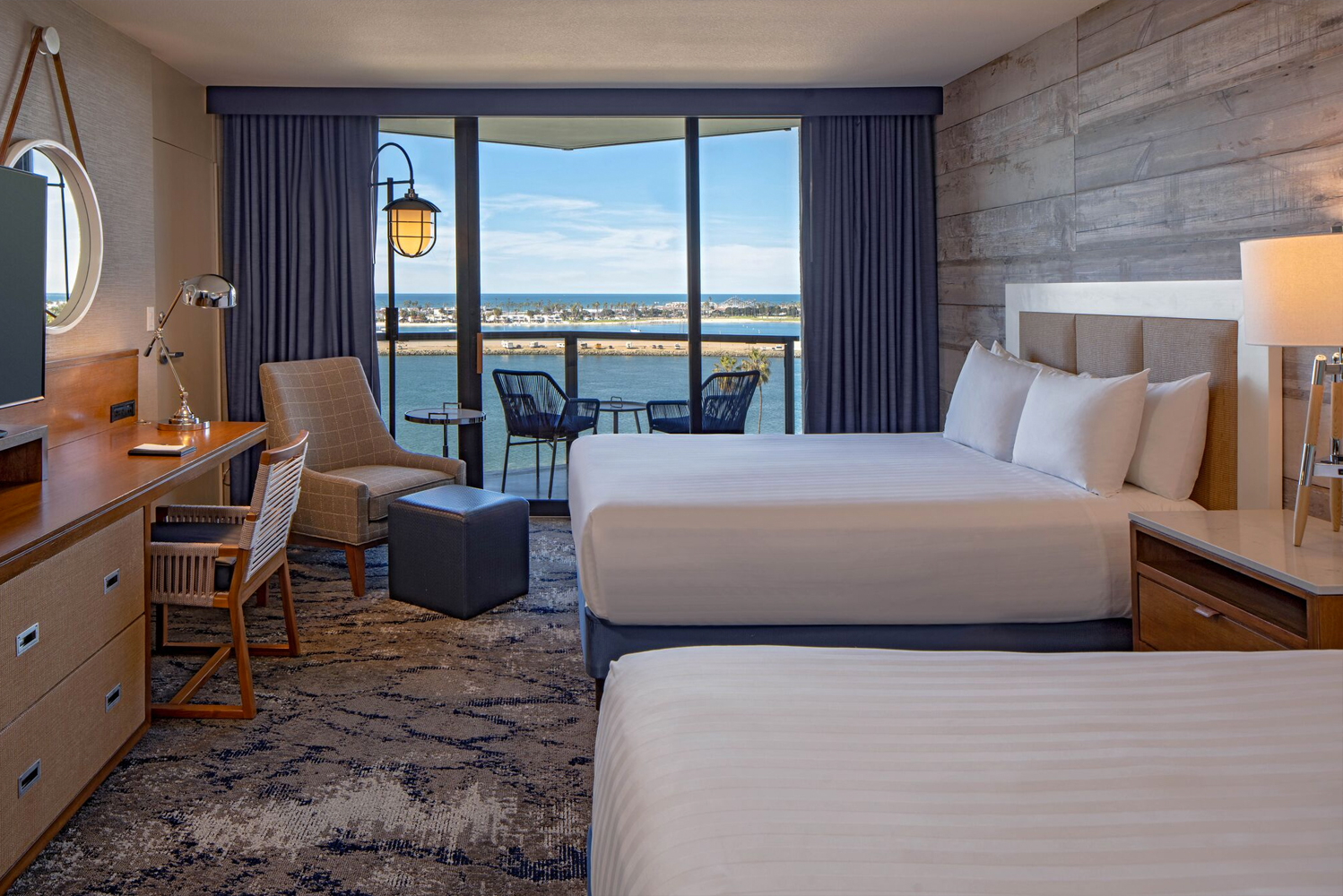 Renovated guestrooms have new wall coverings, including an accent shiplap wall, carpeting and balcony furniture.