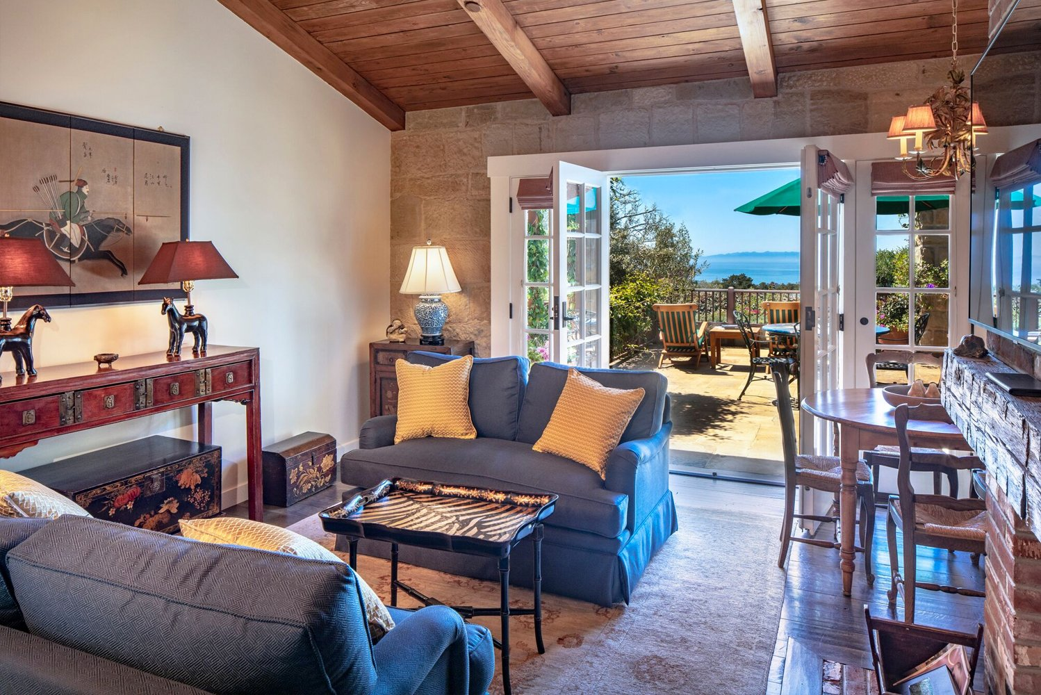 The living room has antiques and French doors that open onto the largest private deck overlooking the Pacific Ocean and Channel Islands.